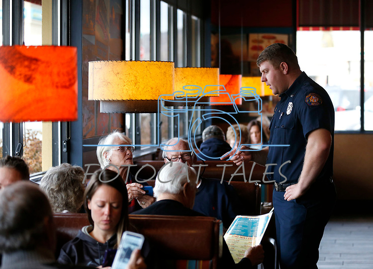Matt Cooper, with Carson City Fire, talks with guests as first responders from around the area wait on diners at Bodines and SlotWorld as part of the Feast with a Hero fundraiser in Carson City, Nev., on Saturday, Dec. 15, 2018. <br /> Photo by Cathleen Allison/Nevada Momentum