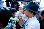 President Correa kisses a baby in a crowded market place in Otavalo Ecuador