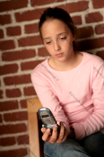 Photo in short focus of a Preteen Girl checking messages on her Mobile Phone. The Phone is in focus while the Girl's face is out of focus.