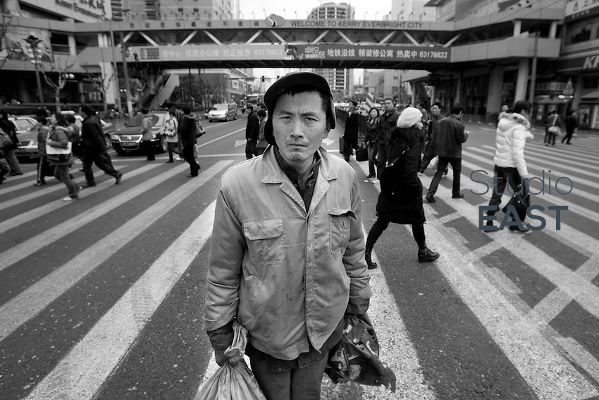 While wealthier Shanghai inhabitants cross the street, Wu Wenyi poses for a photograph, in Shanghai, China, on February 17, 2009. Wu Wenyi came to Shanghai from Quanjiao, Anhui province two months ago to find construction work but failed. During his stay in Shanghai, all his money, 200 RMB (eq. 23 euros) was stolen. Now Wu hangs out in Shanghai trainstation, willing to go back home, but having no money to buy the train ticket. Photo by Lucas Schifres/Pictobank