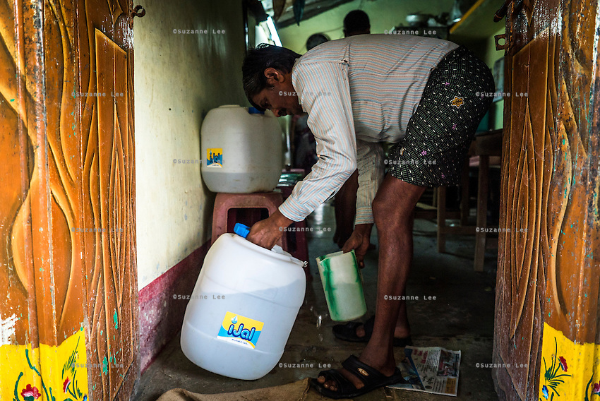 Customers refill the drinking water jugs at Lavanya Gattu's food stall in Peddapur, a remote village in Warangal, Telangana, India, on 22nd March 2015. Lavanya buys iJal water and uses it for all her family consumption, and also cooks with it in her stall and serves it for free to customers who come to eat there. She leaves the iJal water cans at the door, showing off to her customers that she uses safe water. Photo by Suzanne Lee/Panos Pictures for Safe Water Network
