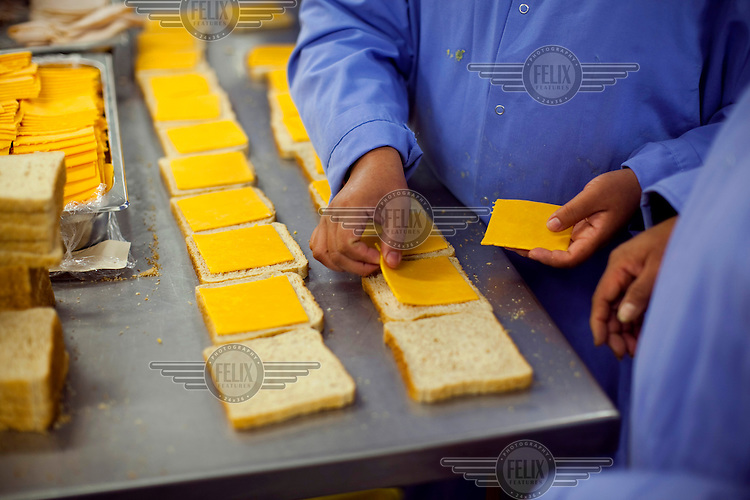A worker at Greencore's Cincinnati facility adds cheese slices to sandwiches. Greencore Group is an Irish-based company that produces convenience foods and sandwiches throughout Britain and Europe. In 2008 Greencore acquired Home Made Brand Foods in Newburyport, Massachusetts to establish Greencore North America.