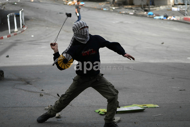 A Palestinian protester hurls stones at Israeli riot police during clashes in the West Bank city of Hebron, 14 March 2013. Photo by Mamoun Wazwaz