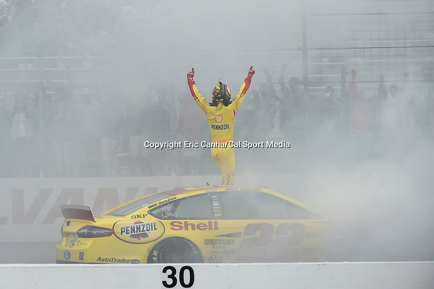 September 21, 2014 - Loudon, New Hampshire, U.S. - Sprint Cup Series driver Joey Logano (22) stands on his car to celebrate his victory with fans at the Nascar Sprint Cup Series Sylvania 300 race held at the New Hampshire Motor Speedway in Loudon, New Hampshire.   Eric Canha/CSM