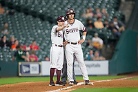 Mississippi State Bulldogs assistant coach Mike Brown (left) points Tanner Poole (12) to the dugout for the sign during the game against the Houston Cougars in game six of the 2018 Shriners Hospitals for Children College Classic at Minute Maid Park on March 3, 2018 in Houston, Texas. The Bulldogs defeated the Cougars 3-2 in 12 innings. (Brian Westerholt/Four Seam Images)