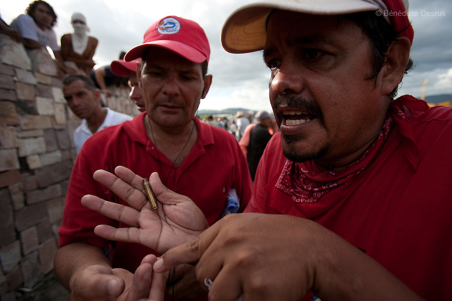 5 July 2009 - Tegucigalpa, Honduras  Supporters of ousted Honduras' President Manuel Zelaya holds bullets shot by soldiers at the protesters at the international airport in Tegucigalpa. At least one person was killed and ten were badly wounded when protesters demanding the return of ousted Honduran President Manuel Zelaya clashed with troops at the Tegucigalpa airport. Zelaya turned back from an attempted return home on Sunday after soldiers clashed with his supporters as he tried to land, fueling tensions over the coup that toppled him. Photo credit: Benedicte Desrus