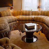 An unusual circular sofa with a round glass-topped coffee table furnishes this cosy sitting room