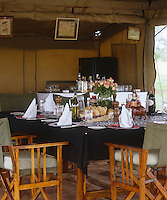A table and bar are ready for lunch in the dining tent of the safari camp