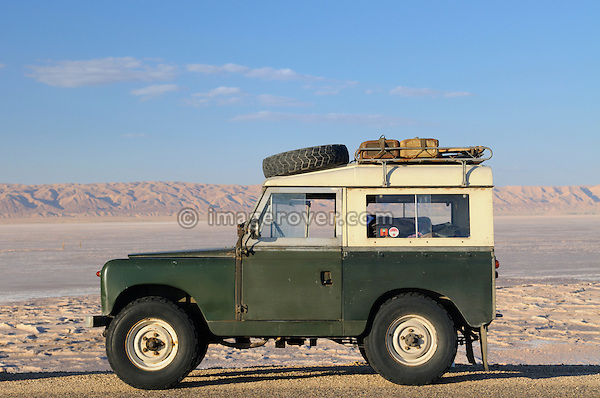 Africa, Tunisia, Chott el Jerid between Kebili and Tozeur. 1962 Land Rover 88 Series 2a with roof rack on the roadway through the Chott el Jerid in southern Tunisia. --- No releases available, but releases may not be needed for certain uses. Automotive trademarks are the property of the trademark holder, authorization may be needed for some uses.