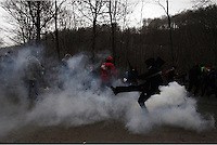 Skouries, Greece Sunday 23 November 2014<br /> Pictured: A teargas canister explodes amongst protesters<br /> Re: Riot police called to break up a protest by local residents against a Canadian-run goldmine in Skouries, in the Chalkidiki area. Eldorado firm has been accused of dumping toxic waste generated during gold processing in northern Greece, into local rivers. Teargas was used by the police to disperse the protesters who retaliated with pyrotechnics.