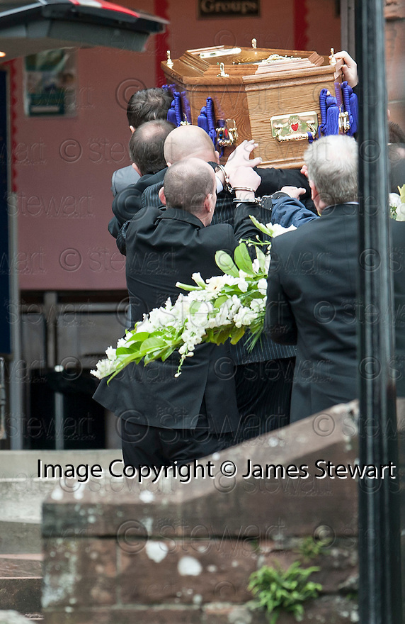 Hugh Haney, still handcuffed to a G4S officer, touches the back of  the coffin of former crime family matriarch Mags Haney as it's carried into St Mary's RC Church in Stirling.