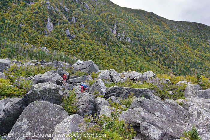 Hikers ascending the Subway Trail in King Ravine. The Subway Trail is a side trail off the King Ravine Trail, which travels through a large boulder field in King Ravine in the White Mountains, New Hampshire USA. The subway trail reconnects with the King Ravine Trail and snow can be found in the ice caves of this ravine during the summer months.