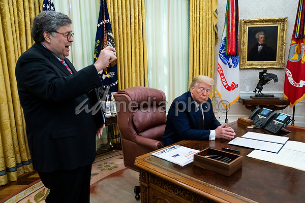 United States Attorney General William P. Barr, left, accompanied by US President Donald J. Trump, right, makes remarks before the president signed an executive order in the Oval Office of the White House in Washington, DC that will punish Facebook, Google and Twitter for the way they police content online, Thursday, May 28, 2020. <br /> Credit: Doug Mills / Pool via CNP/AdMedia