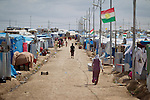 Syrian refugees are seen inside the Domiz refugee camp in Iraqi-Kurdistan. The camp, run by the UNHCR and International Rescue Committee, is home to around 4,500 refugees who have fled from the ongoing Syrian civil war with up to 400 new inhabitants arriving every day.  Built on the site of a former Iraqi Army base that was bombed during the 2003 Coalition forces invasion of Iraq, the camp was cleared of cluster bombs and unexploded ordnance by the Mines Advisory Group (MAG), a demining NGO working in Iraqi-Kurdistan.