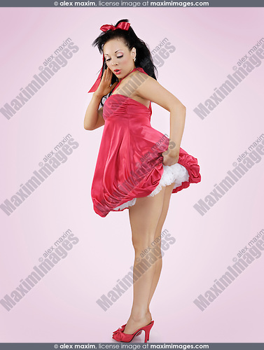 Sexy young woman holding her red dress in the wind