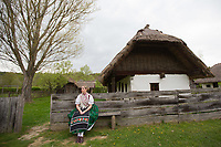 Girl wearing a traditional dress sits outside a farm house in the Skansen open air ethnographic museum in Szenna (about 200 km South-West of capital city Budapest), Hungary on April 14, 2017. ATTILA VOLGYI