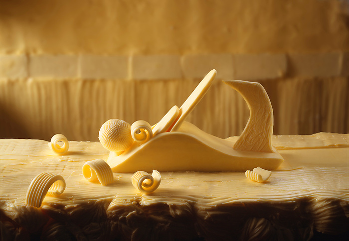 Conceptual butter curler made out of butter on a bitter worktop with butter curls. Funky Stock photos library.