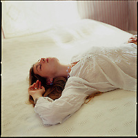 Girl, laying on top of bed facing up with eyes closed