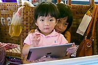 Phnom Penh, Cambodia. Central Market. Kids with iPad.