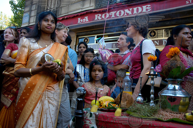 The annual Hindu Ganesh festival in Paris, in which temple gods are paraded through the streets of the La Chapelle district in the 18th arrondissement. Tamil family waiting outside a bar, for the passage of Ganesh, to give offerings and receive blessings.