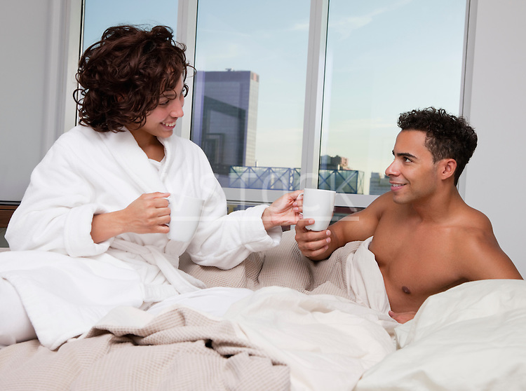 USA, New York City, couple drinking morning coffee in bed