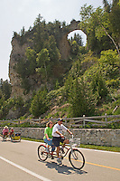 Tourists on Mackinac Island in Michigan ride a tandem bicycle beneath Arch Rock while touring the island.