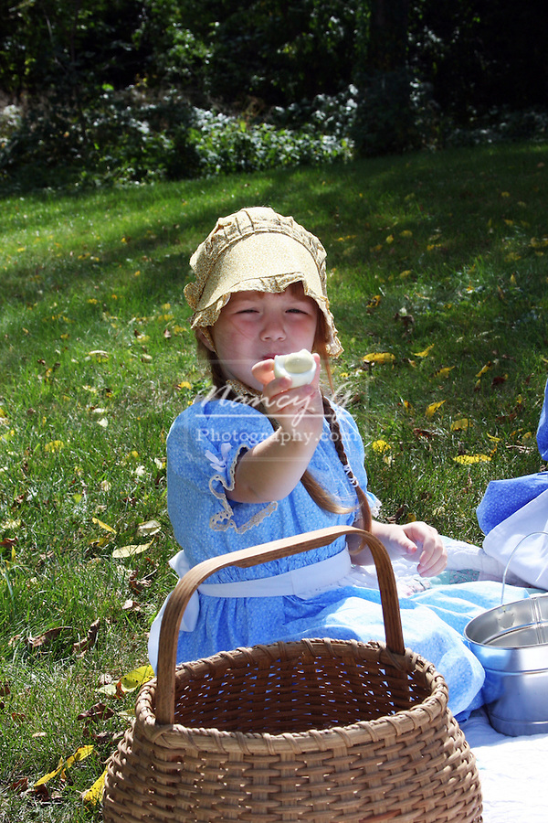 A young girl eating a hard boiled egg at a picnic