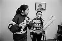 Albania. Tirana. Orjeta Mishani (right) is a professional musician and a member of the Orchestra Frymore which is the only Albanian military brass band. In order to improve her living and earn money, she has a second job as music's tutor teaching private flute lessons at home. A pupil plays flute while looking at notes. The flute is a wind instrument made from a tube with holes along it that are stopped by the fingers or keys, held vertically or horizontally so that the player's breath strikes a narrow edge. The modern orchestral form, typically made of metal, is held horizontally and has an elaborate set of keys. Tirana is the capital and largest city of Republic of Albania. 22.11.1998 © 1998 Didier Ruef