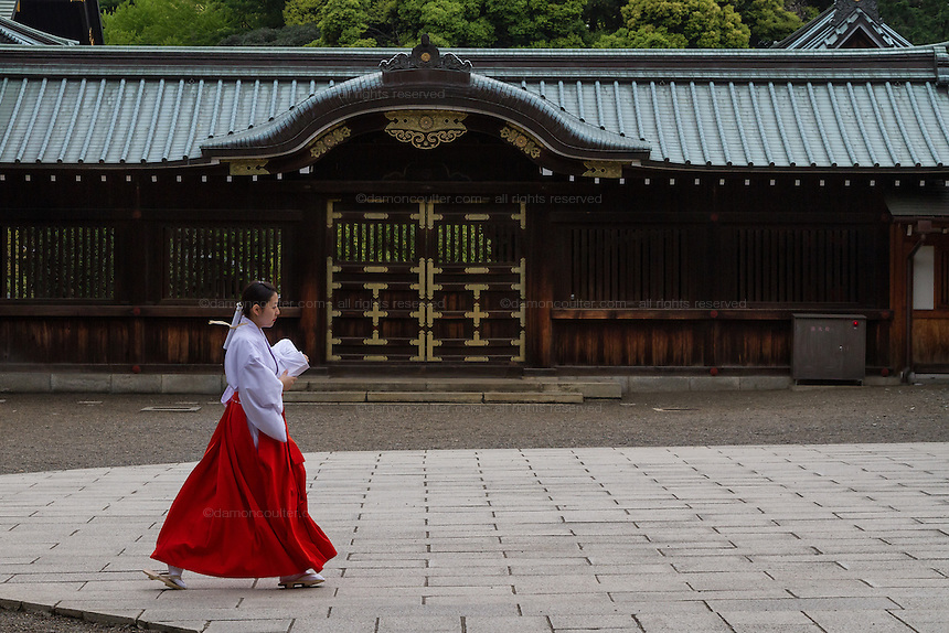 A shrine maiden in red and white robes crosses a courtyard at the controversial Yasukuni Shrine in Kudanshita, Tokyo, Japan. Monday May 2nd 2016