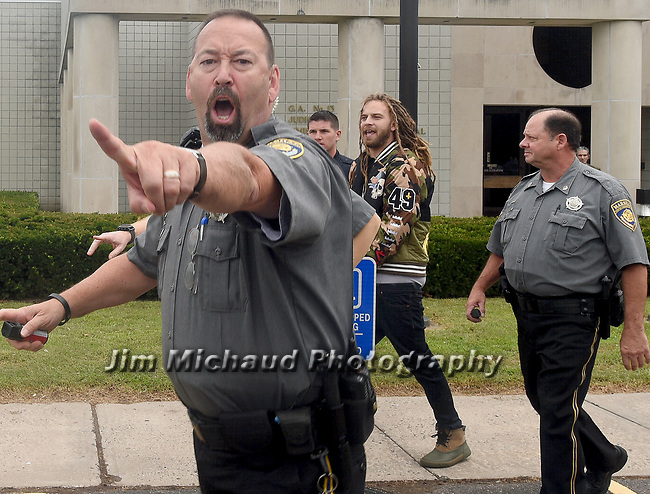 Police and court marshals work to clear the area as a man is taken away for fighting after a fight broke out outside the courthouse during arraignment for Shyhiem Adams at Enfield Superior Court on charges in the stabbing death of 16-year-old of Justin Brady, Tuesday, Sept. 11, 2018, in Enfield, Conn. One person was arrested. (Jim Michaud/Journal Inquirer via AP, Pool)