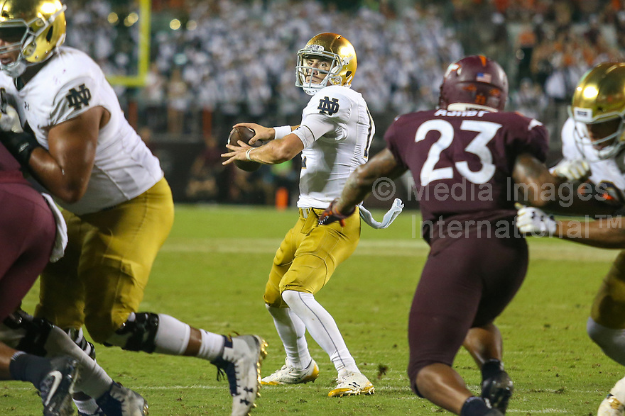 Blacksburg, VA - October 6, 2018: Notre Dame Fighting Irish quarterback Ian Book (12) throws a touchdown during the game between Notre Dame and VA Tech at  Lane Stadium in Blacksburg, VA.   (Photo by Elliott Brown/Media Images International)