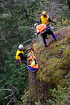 Jefferson Search and Rescue conducts an over the cliff training exercise by lowering and  raising a litter, containing a volunteer victim, in a simulated rescue from the bottom of a 400 foot cliff. The training site is near Gibbs Lake in the Olympic National Forest. The team, made up of volunteers from the surrounding communities, meets monthly to hone their skills.