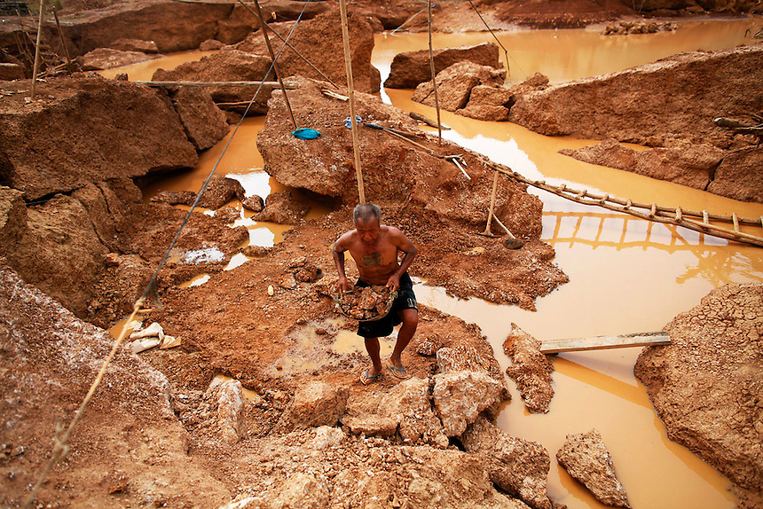 A man carries a load of stones to break at a primitive gold mine in Panompa near Phichin February 17, 2011. A group of Thais use primitive tools and methods to extract gold from self-run mines near the countries biggest and most modern Chatree gold mine. A family working at the mine can get around one gram of gold per day they sell at the site for about 1000 Thai bahts (32 USD).   REUTERS/Damir Sagolj (THAILAND)