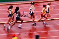 Blurred action image of a female runners at a track meet.