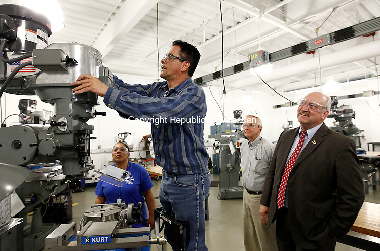 Waterbury, CT- 24 April 2014-042414CM03- Naugatuck Valley Community College manufacturing students, Armando Rodriguez of Waterbury, center, and Priscilla Rodriguez of Waterbury,  give a demonstration on a Bridgeport Vertical Milling machine at the college in Waterbury on Thursday.  Looking on is Ed Tremblay, treasurer with the local Precision Metalforming Association, left, and Bill Adler chairman of the Board of Directors of The Precision Metalforming Association .  The college's Advanced Manufacturing Program received a grant from the Precision Manufacturing Association Educational Foundation.  The grant will help recruit future students into the program.    Christopher Massa Republican-American