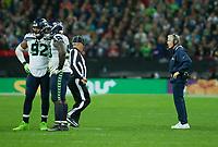 Seattle Seahawks coach Pete Carroll talks to a line judge
