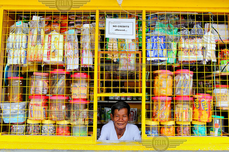 A shopkeeper looks out from behind the yellow metal grill that protects his small premises. Pinned above him is a small notice that reads: 'NO CREDITS allowed...'.