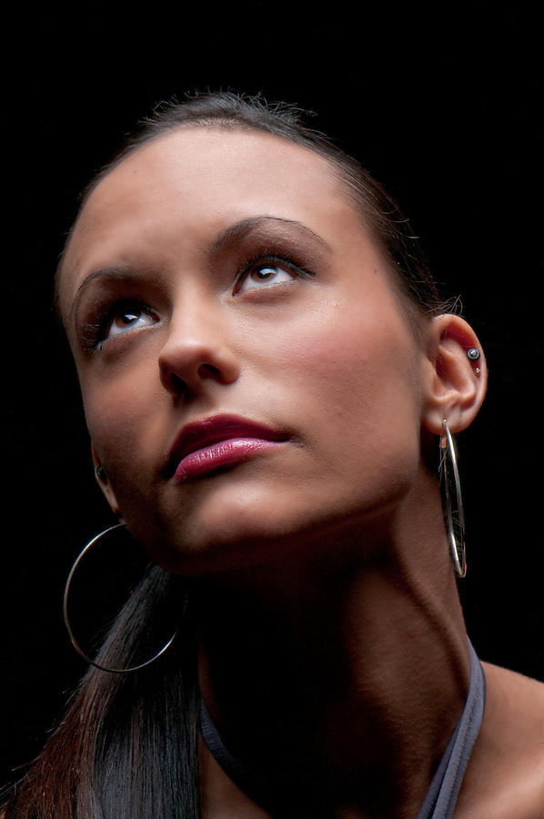 Portrait of young attractive caucasian woman looking up in dramatic light. Black Background.