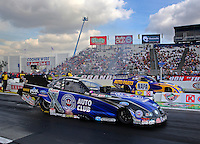 Feb 7, 2014; Pomona, CA, USA; NHRA funny car driver Robert Hight (near lane) races alongside Ron Capps during qualifying for the Winternationals at Auto Club Raceway at Pomona. Mandatory Credit: Mark J. Rebilas-