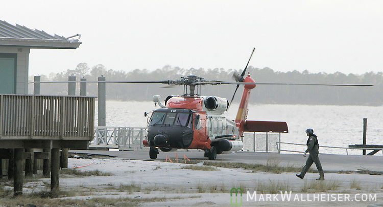 The pilot of a United States Coast Guard helicopter walks back to his aircraft after landing on Navarre Beach July 11, 2005 to talk to law enforcement officials the day after Hurricane Dennis came ashore here.