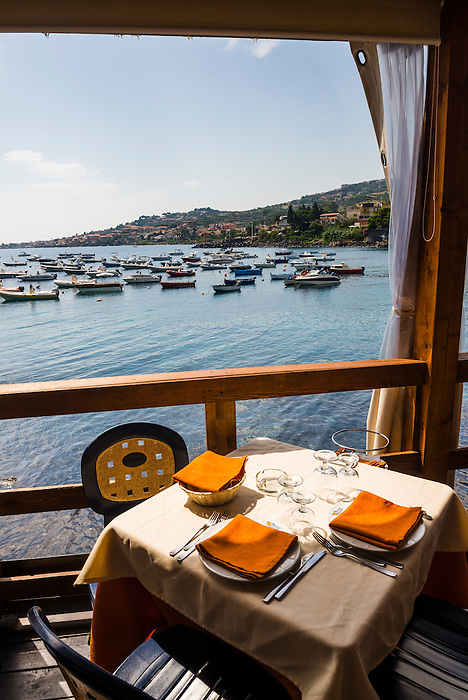 Cafe by the Mediterranean Sea, with boats in the harbour at Aci Trezza, just outside Catania, Sicily, Italy, Europe. This is a photo of a cafe by the Mediterranean Sea with boats in the harbour at Aci Trezza, just outside Catania, Sicily, Italy, Europe