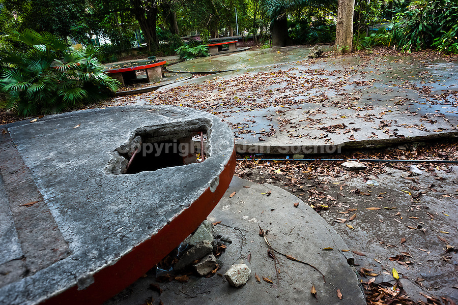 A ruined concrete picnic table area at the Havana Zoo, Havana, Cuba, 12 February 2011. The largest and the oldest zoo in Cuba (founded in 1939) is located in a centric neighborhood of the capital. Since the 1990s Cuba struggles with chronic economic crisis and therefore the strong marks of rundown and lack of sources are evident within the whole zoological garden. A lot of cages are empty and out of use for long time, the remaining animals are captured in poorly maintained pits. Concrete enclosures have no vegetation, all facilities are unkept. The food supply is often inadequate and visitors throw junkfood to the animals because there are no zookeepers around.