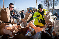 Westerville fire fighters load bags of collected food items into containers at the W.A.R.M. warehouse on East Broadway. The bags of nonperishable food were collected by volunteers in each neighborhood in the city.