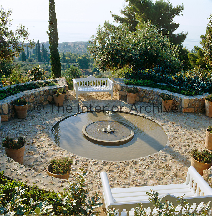 The herb garden is centred around a circular pool and cobbled terrace with Turkish benches designed by John Stefanidis