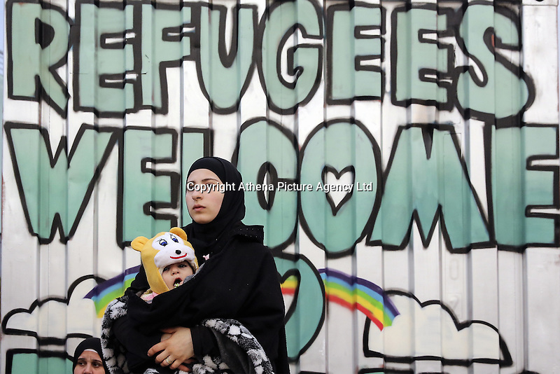 "Pictured: A young mother clutching her baby stands against a ""Refugees Welcome"" graffitiwalks at the port of Piraeus Friday 26 February 2016<br /> Re: Hundreds of refugees that crossed the border from Turkey to the Greek islands, have arrived at the port of Piraeus near Athens, Greece"