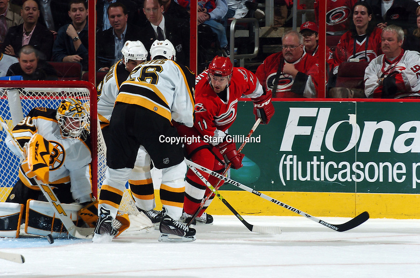 Carolina Hurricanes' Justin Williams passes through the crease defended by the Boston Bruins' Brad Boyes (26) and goaltender Tim Thomas during their game at the RBC Center in Raleigh, NC Wednesday, March 1, 2006. The Hurricanes won 4-3..