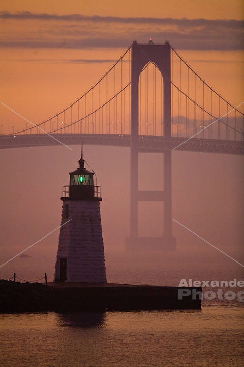 USA, Newport, RI - The green glow of the Newport Harbor lighthouse on Goat Island contrasts with the mauve and orange tones of a foggy Newport sunset.