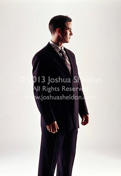 Caucasian looking man wearing a dark business suit looking sideways