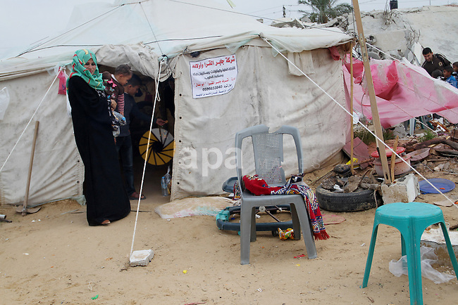 A Palestinian woman, whose house was destroyed by what witnesses said was Israel shelling during a 50-day conflict last summer, stands outside her tent east of Khan Younis in the southern Gaza Strip January 27, 2015. The main U.N. aid agency in the Gaza Strip said on Tuesday a lack of international funding had forced it to suspend payments to tens of thousands of Palestinians for repairs to homes damaged in last summer's war. Robert Turner, Gaza director of operations for the United Nations Relief and Works Agency (UNRWA), said in a statement that UNRWA received only $135 million of the $720 million pledged by donors to its cash assistance program for 96,000 refugee families whose homes were damaged or destroyed in the 50-day conflict between the Hamas Islamist movement and Israel. Photo by Abed Rahim Khatib