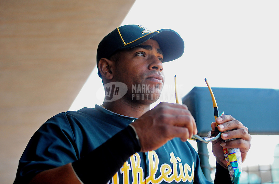 Mar. 19, 2012; Phoenix, AZ, USA; Oakland Athletics outfielder Yoenis Cespedes in the dugout prior to the game against the Arizona Diamondbacks during a spring training game at Phoenix Municipal Stadium.  Mandatory Credit: Mark J. Rebilas-.